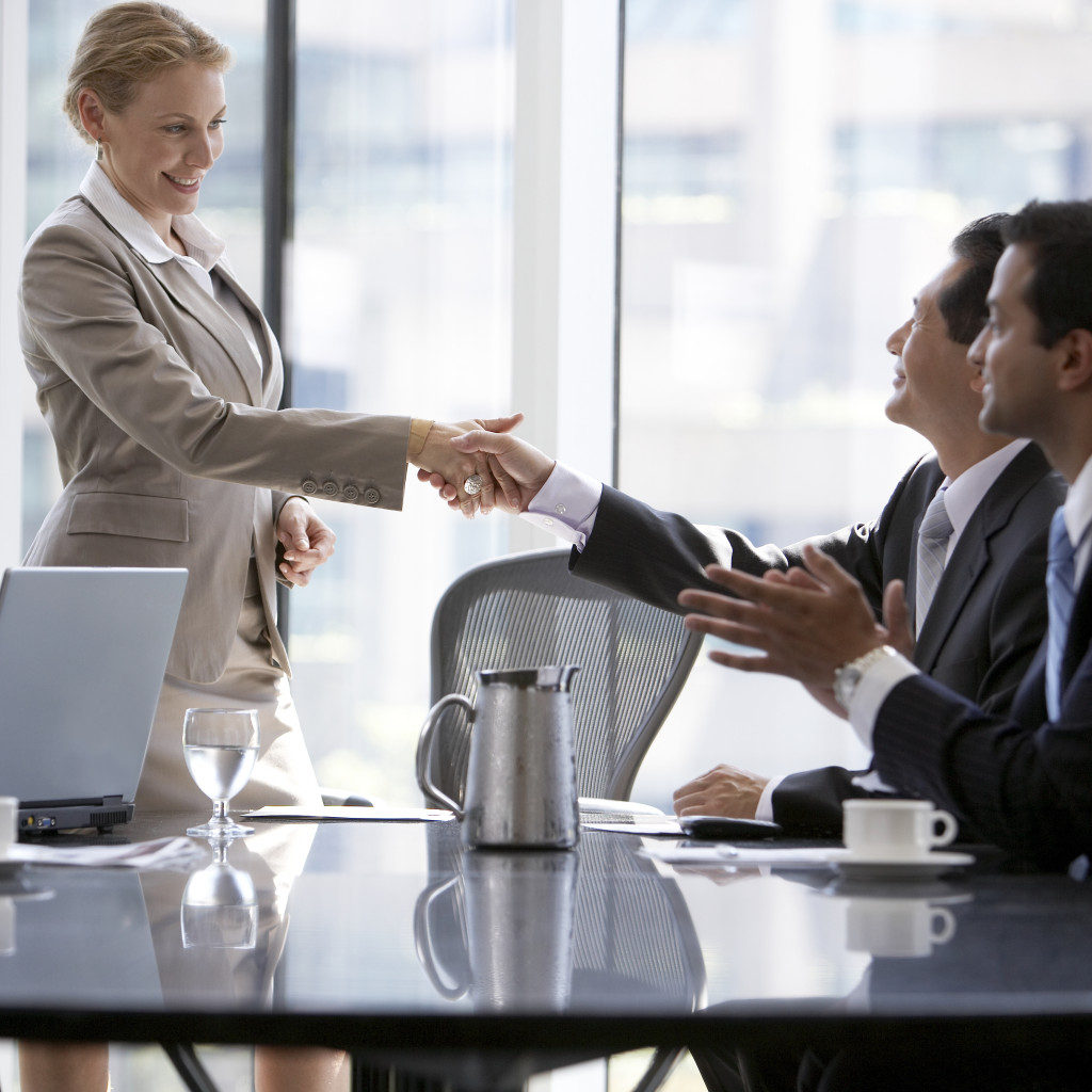 Man and woman shaking hands during business meeting